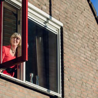 Vrouw in open raam. 3 tips voor ventileren tijdens corona.